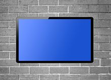 Blank screen LCD tv hanging on a wall stock photography