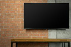 Blank screen Led Tv on red brick wall with empty wooden table. Blank screen Led Tv on red brick wall with media wooden table royalty free stock image
