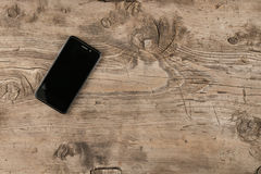 Blank screen mobile phone on wood background. Stock Photo