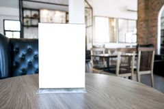 Blank screen mock up menu frame standing on wood table in coffee stock photography