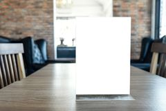 Blank screen mock up menu frame standing on wood table in coffee royalty free stock images