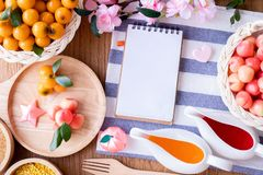 Blank screen on notepad paper and Delectable imitation fruits, Fruit Shaped Mung Beans. Thai traditional dessert stock photo