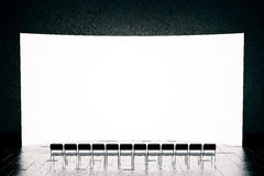 Blank screen and seats. Front view of blank screen and row of seats  in dark interior with reflections on floor. Mock up, 3D Rendering. Presentation concept Royalty Free Stock Image