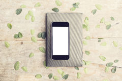 Blank screen of smartphone with leaves and diary on wooden table Stock Images