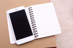 Blank screen smartphone and note book on wooden background Royalty Free Stock Photography