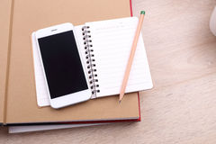 Blank screen smartphone with pencil and note book on wooden back Royalty Free Stock Photos