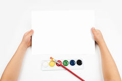 Blank sheet in child hands with watercolors paint Royalty Free Stock Photography