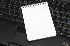 Blank sheet notebook and laptop. Notepad close-up on top of a laptop keyboard Royalty Free Stock Images