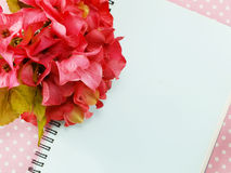 Blank sheet of notebook and red and beautiful hydrangea of artificial flowers background Royalty Free Stock Photo