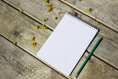 Blank sheet of notepad, pencil, on a wooden old table, yellow flowers Stock Image