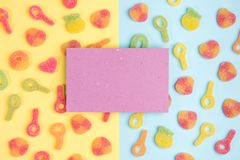 Blank sheet of paper on background of gummy candies. Multicolored candies on yellow and blue backgrounds. Top view stock photos
