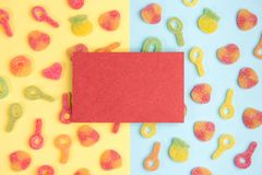 Blank sheet of paper on background of gummy candies. Multicolored candies on yellow and blue backgrounds. Top view royalty free stock photo