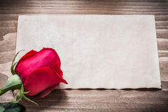 Blank sheet of paper and bloomed rose on wooden board Royalty Free Stock Photo