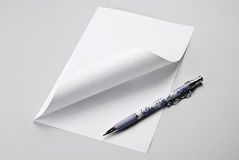Blank sheet of paper with curled corner and pen Stock Photos