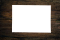 Blank sheet of paper on dark wooden desk. Stock Image