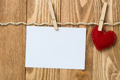 Write some words of love. Blank sheet of paper hand made heart pinned to rope on wooden background Royalty Free Stock Photography
