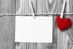 Write some words of love. Blank sheet of paper hand made heart pinned to rope on wooden background Royalty Free Stock Image