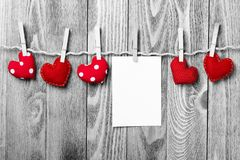 Write some words of love. Blank sheet of paper hand made heart pinned to rope on wooden background Stock Image