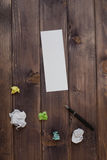 A blank sheet of paper pen and damaged the paper. White clean sheet of paper, a black pen and a broken multi-colored paper on a dark wooden table. the view from stock photos