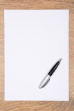 Blank sheet of paper and pen on wooden table Royalty Free Stock Photography