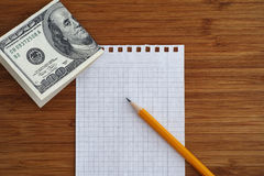 Blank sheet of paper and pencil with one hundred dollars bill on Royalty Free Stock Images