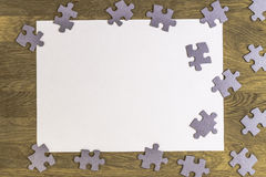 Blank sheet of paper surrounded by puzzle pieces on wooden background. Top view. Copy space for text Royalty Free Stock Photos