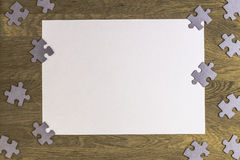 Blank sheet of paper surrounded by puzzle pieces on wooden background. Top view. Copy space for text Royalty Free Stock Images