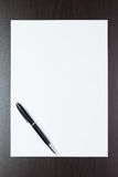 Blank sheet of paper on the table with a pen Royalty Free Stock Photography