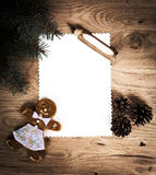 Blank sheet of paper on a wooden floor with a pencil and Christmas decorations with a gingerbread man Royalty Free Stock Photography