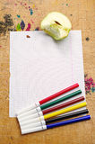 Blank sheet of school notebook and felt-tip pens of different co. Blank sheet of school notebook, felt-tip pens of different colors and slice apple on old wooden stock photo