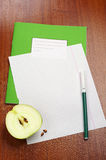Blank sheet of school notebook and slice apple Stock Photos