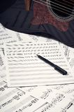 Blank sheets for notes, pen and guitar royalty free stock photos