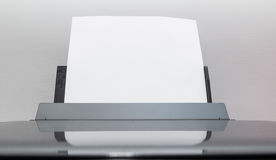 Blank sheets of paper coming out of an computer printer. Royalty Free Stock Image