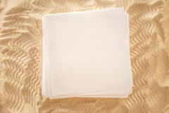 Blank sheets of paper on sand Stock Photography