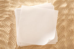 Blank sheets of paper on sand Royalty Free Stock Photo