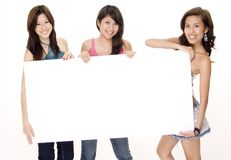 Blank Sign #1. Three attractive young women hold a large blank sign Stock Photos