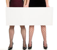 Blank sign. Two women holding a blank sign on a white background Royalty Free Stock Photos