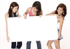 Blank Sign #2. Three attractive young women look at the big blank sign they are holding Stock Images