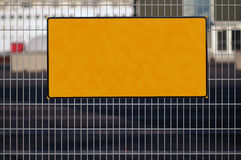 Blank sign. Blank yellow sign on metal fence royalty free stock photo