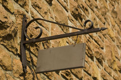 Blank sign. A blank wood sign hanging from a metal support on a stone wall Royalty Free Stock Photos