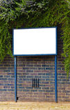 Blank Sign. Surrounded by textured brick wall and green trees Royalty Free Stock Photo