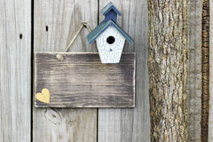 Blank sign with blue and white birdhouse next to tree Royalty Free Stock Photography