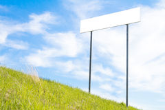 Blank sign board. On a background of green grass and blue sky stock photography