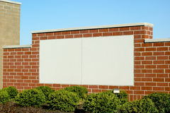 Blank Sign in Brick. Blank brick sign area in white with blue sky background and shrubs in foreground. Allows for adding custom letters and message Stock Photo