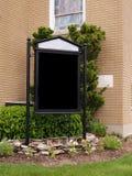 Blank sign by a brick church building Stock Photos