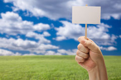 Blank Sign in Fist Over Grass Field and Sky Royalty Free Stock Photography