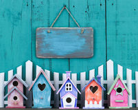 Blank sign hanging over fence and row of birdhouses Stock Image