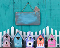 Blank sign hanging over fence and row of birdhouses stock photos