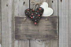 Blank sign hanging on wood door with calico and muslin hearts Stock Images