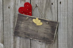 Blank sign hanging on wood door with red and gold hearts Royalty Free Stock Photos